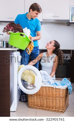 happy spouses doing regular laundry and smiling at home - stock photo
