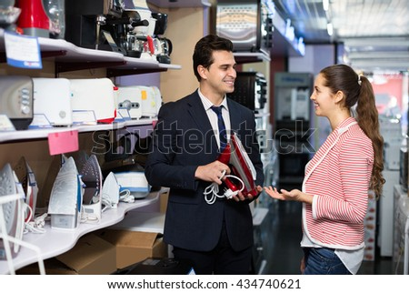 Happy spouses 35s choosing new clothes iron in supermarket