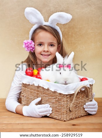 Happy spring girl with easter basket - holding colorful eggs and white rabbit - stock photo