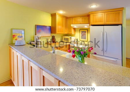 Happy spring kitchen with tulips and yellow green walls. - stock photo