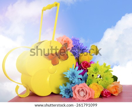 Happy Springtime Spring colorful roses and daisy flowers with yellow vintage style watering can and sky background with applied filters and sun lens flare. - stock photo