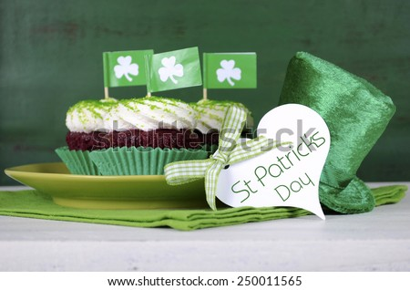 Happy St Patricks Day cupcakes with green theme decorations on vintage style green wood background. - stock photo