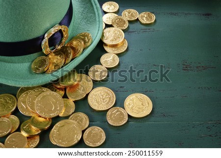 Happy St Patricks Day leprechaun hat with gold chocolate coins on vintage style green wood background with copy space. . - stock photo