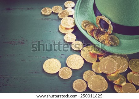 Happy St Patricks Day leprechaun hat with gold chocolate coins on vintage style green wood background, with retro vintage style filters. - stock photo