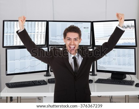 Happy stock broker laughing while standing with arms outstretched in office - stock photo