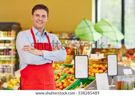Happy store manager in supermarket with his arms crossed