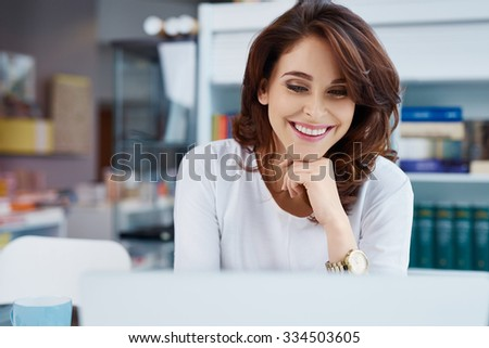 Happy store manager working on laptop - stock photo