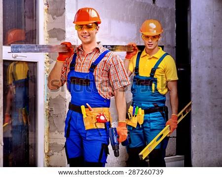 Happy strong men in builder uniform. - stock photo
