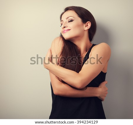 Happy strong sporty woman hugging herself with natural emotional enjoying face. Love concept of yourself body