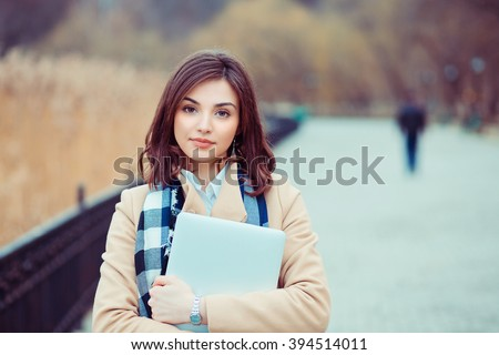 Happy student. Closeup portrait headshot professional beautiful confident young business woman holding computer isolated park cityscape outdoor background. Multicultural mixt race asian russian model - stock photo
