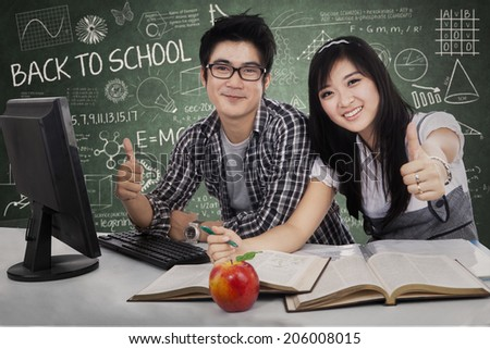 Happy student couple winning with computer on the desk - stock photo