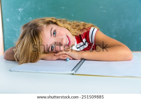 Happy student expression schoolgirl in classroom desk at school green chalk board - stock photo