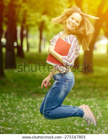 Happy student girl jumping for joy after passed exam - stock photo