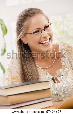 Happy student girl sitting at desk with pile of books, reading. - stock photo