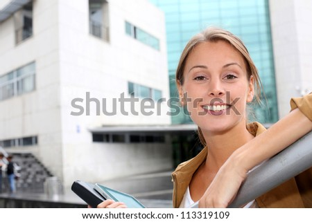 Happy student girl standing in front of college building - stock photo