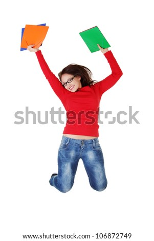Happy student girl wearing jeans and glasses is jumping with folders in her hands. Isolated on white background.
