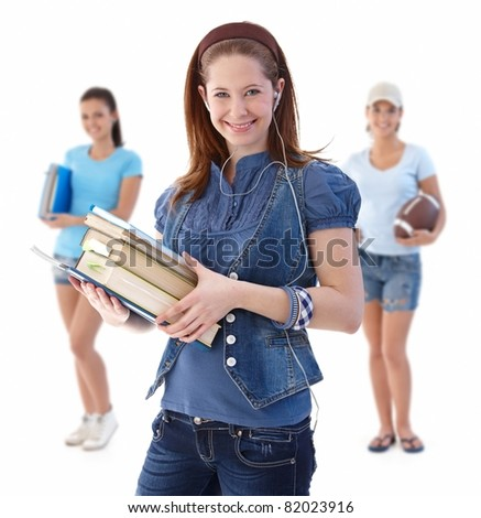 Happy student girl with classmates in background, looking at camera, smiling, isolated on white.? - stock photo