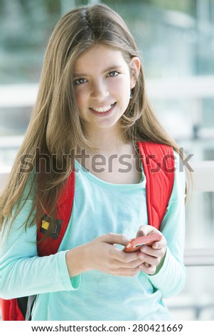 Happy student girl with mobile phone, sending text message - stock photo
