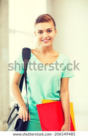 happy student girl with school bag and color folders