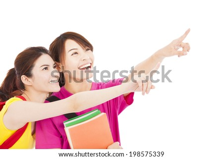 happy student girls holding books and pointing somewhere - stock photo
