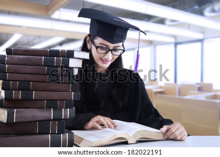 Happy student in graduation cap is reading books at reading room - stock photo