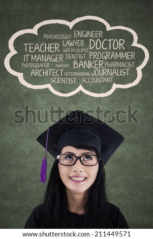 Happy student in graduation cap with her dream on the blackboard - stock photo