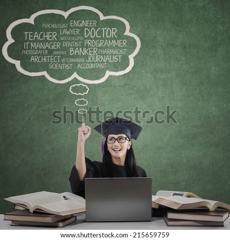 Happy student in graduation cap with her future career - stock photo