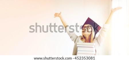 happy student in graduation cap with stack of books - stock photo