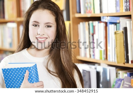 Happy student in the library with book