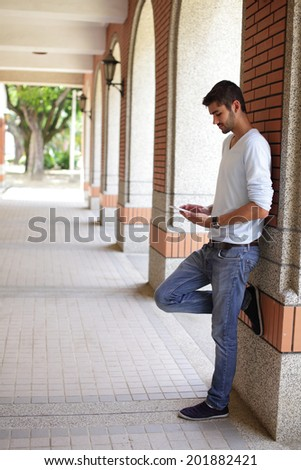 Happy Student man learning with a touch pad on campus, caucasian