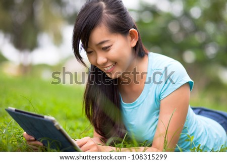 Happy student preparing for lessons in the park - stock photo