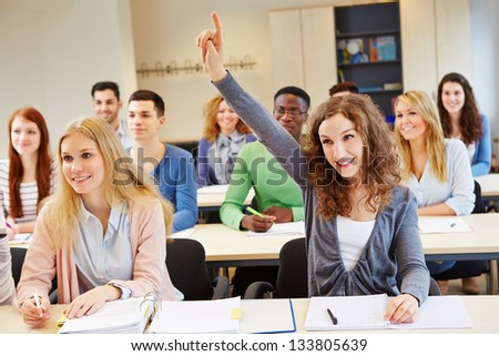 Happy student raising her hand and answering question in university class - stock photo