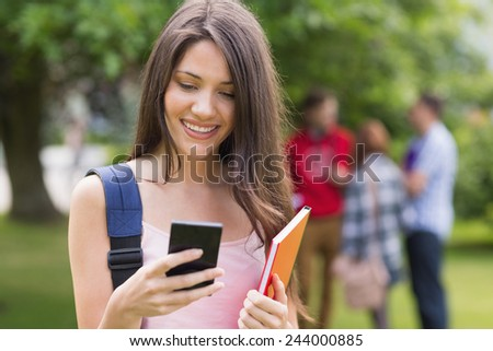 Happy student sending a text outside on campus at the university