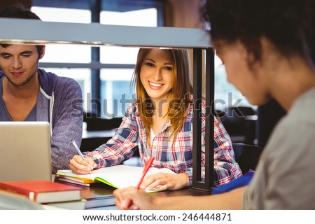 Happy student sitting at desk writing smiling at camera in library