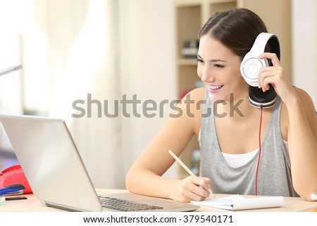 Happy student studying watching video lecture on line and listening with headphones and taking notes sitting in a desktop at home - stock photo