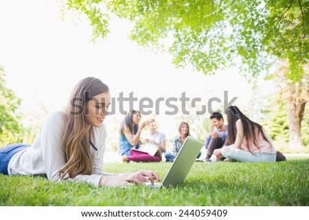 Happy student using her laptop outside at the university - stock photo