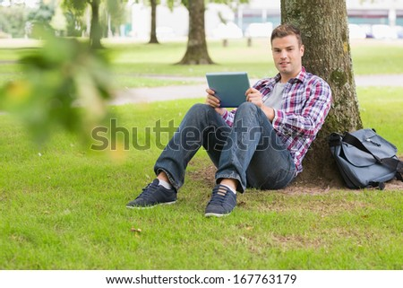 Happy student using his tablet pc outside leaning on tree on college campus