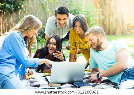 Happy student using laptop in campus - stock photo