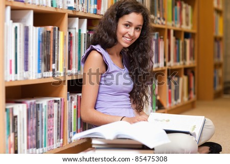 Happy student with a book in a library