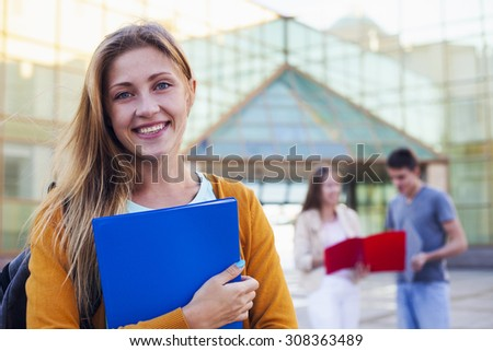 Happy student with folder next college on the background of friends. Education concept - stock photo