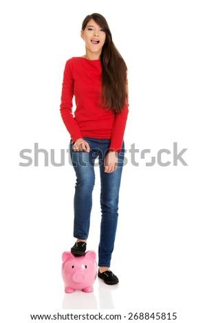 Happy student woman with piggybank under leg. - stock photo