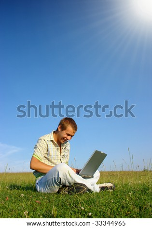Happy student working with laptop on green meadow, summer sunny day - stock photo