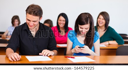 Happy students at their desks laughing before taking an exam. - stock photo
