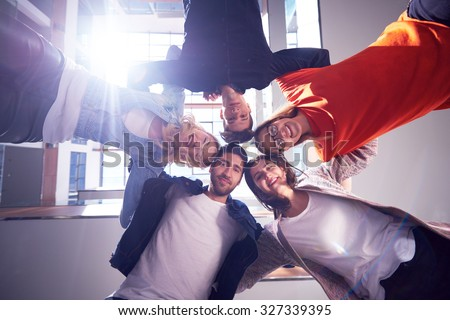 happy students celebrate, friends group together at school,  young people raise hands, stack and get in circle  formation together - stock photo