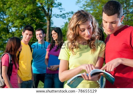 Happy students discussing together with book outdoor in the college park - stock photo