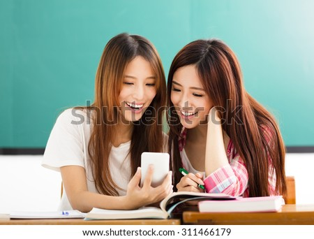 happy students girls watching the smart phone in classroom