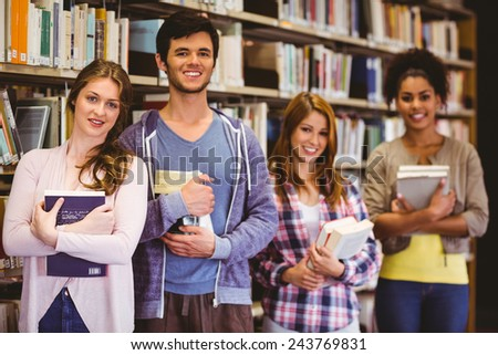 Happy students holding books in row in library - stock photo