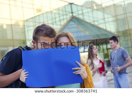 Happy students holding folders- making fun. Education concept - stock photo