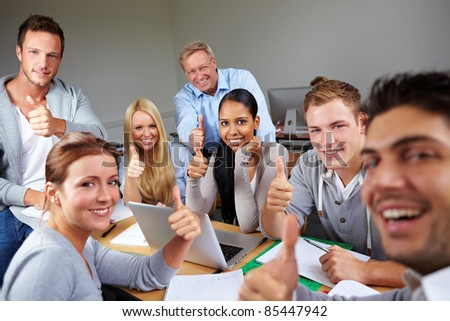 Happy students holding thumbs up in university - stock photo