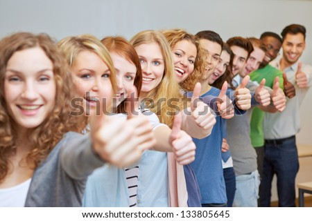 Happy students in a row holding their thumbs up - stock photo